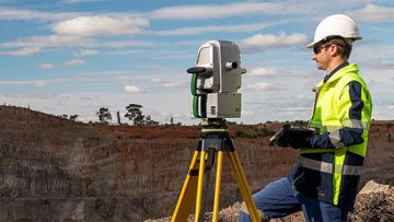 A Maptek XR3 laser scanner being operated by someone with a tablet on a mine site.